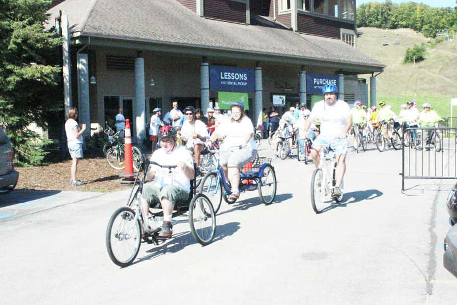 "AT THE STARTING LINE: The ""Yes We Can"" event at the Bike Benzie Tour gets going as the riders pass the starting line. Bikes and tricycles were available for the riders, many who had special needs, but the event let them enjoy the roads. (Photo/Bryan Warrick)"