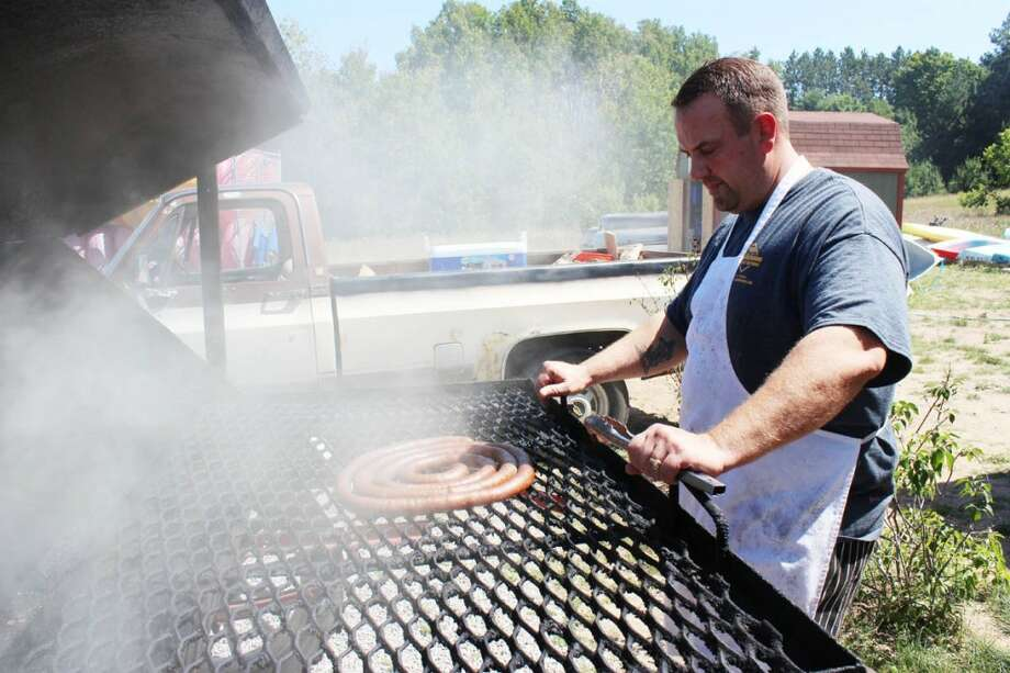 SMOKED: Walt Lagille of Walt's Smokehouse and Specialty Meats retrieves a fresh batch of bratwurst from the smoker. Aside from smoked meats, Walt's also offers made-to-order cuts of meat, like an old-fashioned butcher shop. (Photo/Colin Merry)