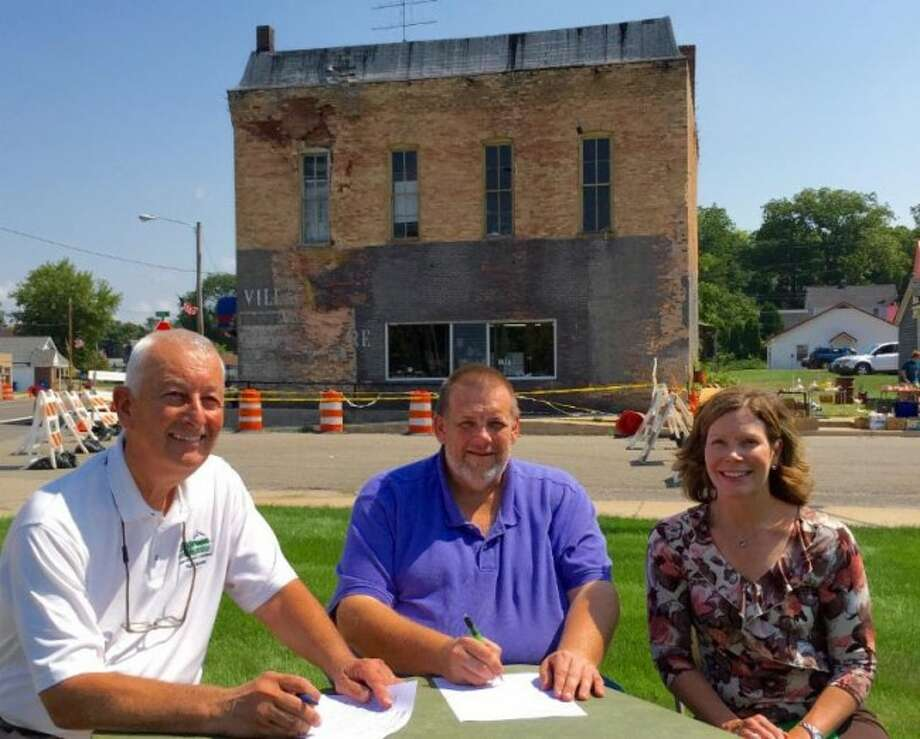 BLIGHT CONTROL: The Village of Bear Lake established a fund at the Manistee County Community Foundation to provide a way for people to make charitable contributions in support of eliminating blight conditions in the Village, such as this building on US 31. Pictured left to right: Rick Farfsing, Community and Business Alliance; Jeff Bair, president of the Village of Bear Lake and Laura Heintzelman, executive director of the Manistee County Community Foundation.