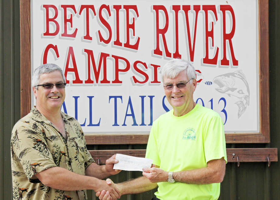 MUTUALLY BENEFICIAL: Kris Welty, who owns the Betsie River Campsite,  presents John Ester, president of the Friends of the Betsie Valley Trail, with a check for nearly $1,200. (Courtesy Photo)