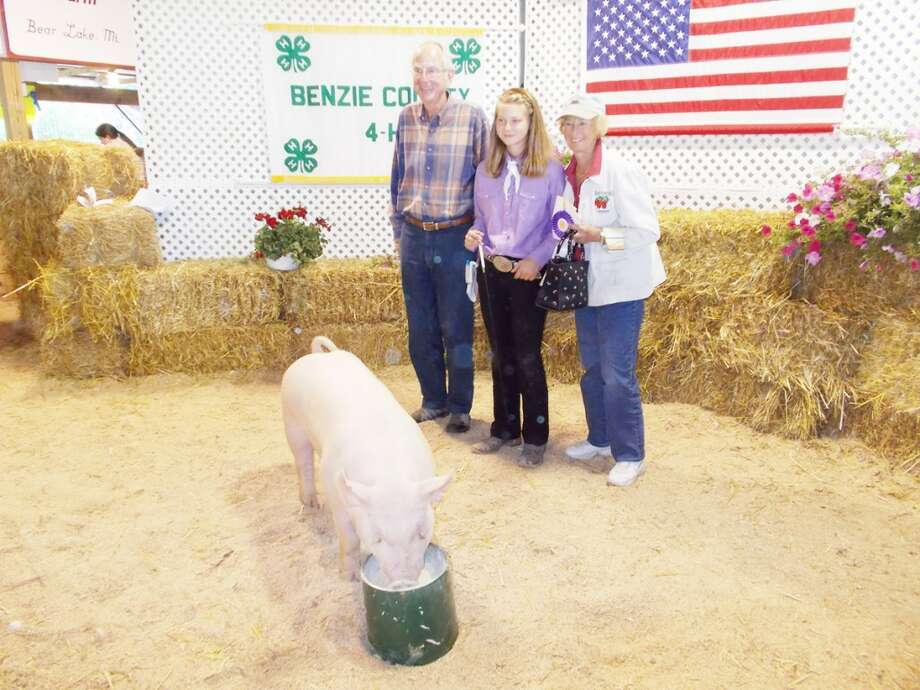BACON FOR BACN: Phil and Nancy Meek purchased Maggie Domres' pig at the Manistee County 4-H Auction. The pig, named New York, is destined to help area neighbors in need at the Benzie Area Christian Neighbors food pantry. (Courtesy photo).