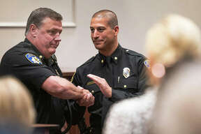 Former Alton Police Department deputy chief Terry Buhs accepts a standing ovation and a warm handshake from incoming deputy chief, Marcos Pulido, during a ceremony held Thursday at the Alton Police Department. Buhs departs after 30 years on the force for, perhaps, calmer digs as the City of Alton's director of code enforcement.