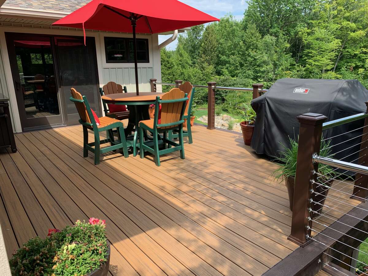 A deck designed by Curtis Lumber in Lake George using Trex products. The composite material, made with reclaimed wood, sawdust and recycled plastic, is more durable and needs less maintenance. Deck furniture, like the table and chairs shown here, is also made with composite materials. (Photo by Jim Carpenter/Curtis Lumber)