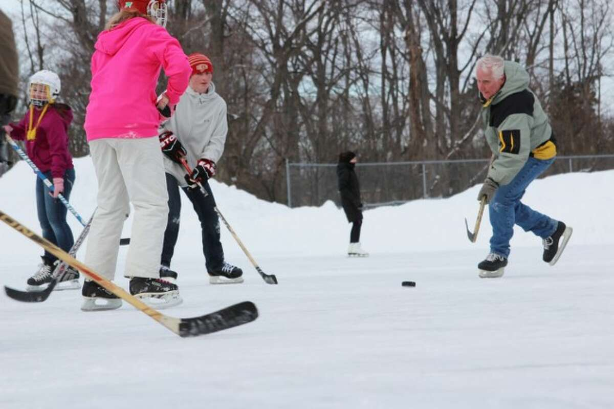 GOING FOR IT: Players of all ages make a break for the puck during a pick-up game at the Benzonia Ice Rink.