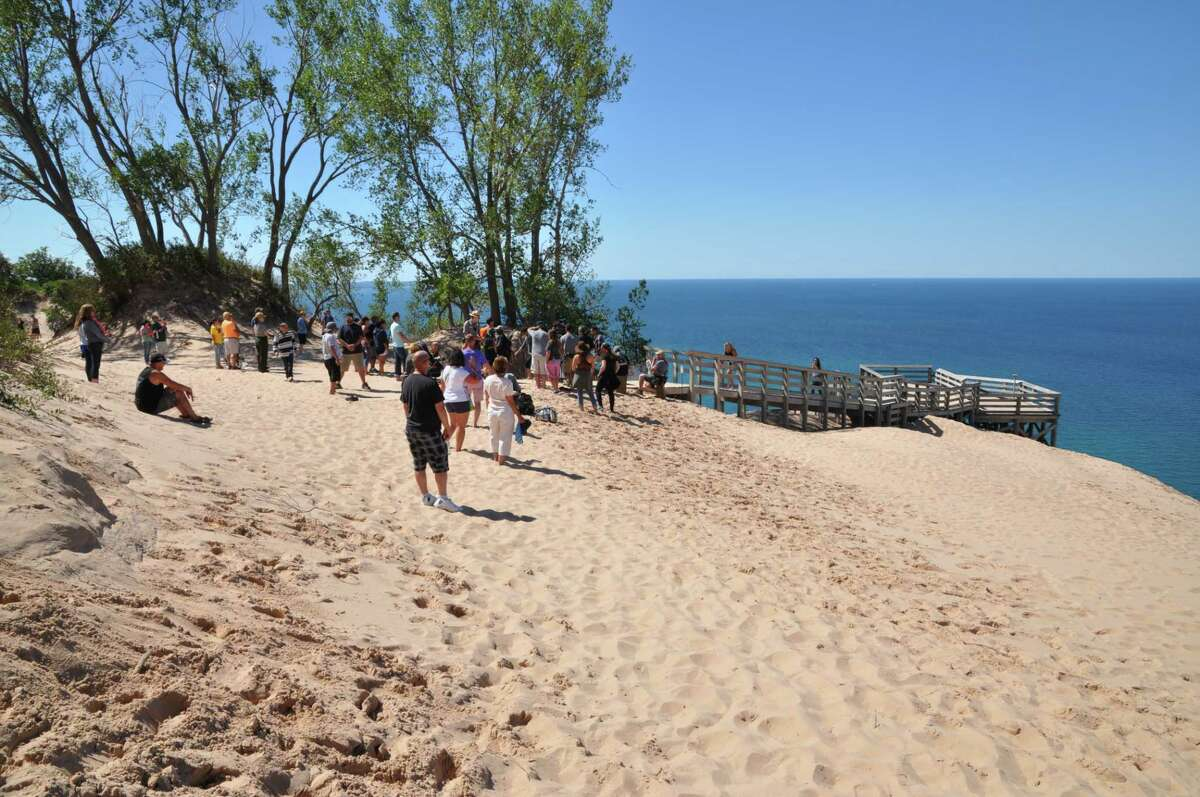 """RECORD SETTING: Visitors enjoy a view of Lake Michigan from the """"back"""" of the Sleeping Bear Dunes in 2015, a year that saw a record-breaking number of visitors to the Sleeping Bear Dunes National Lakeshore. (Courtesy Photo)"""