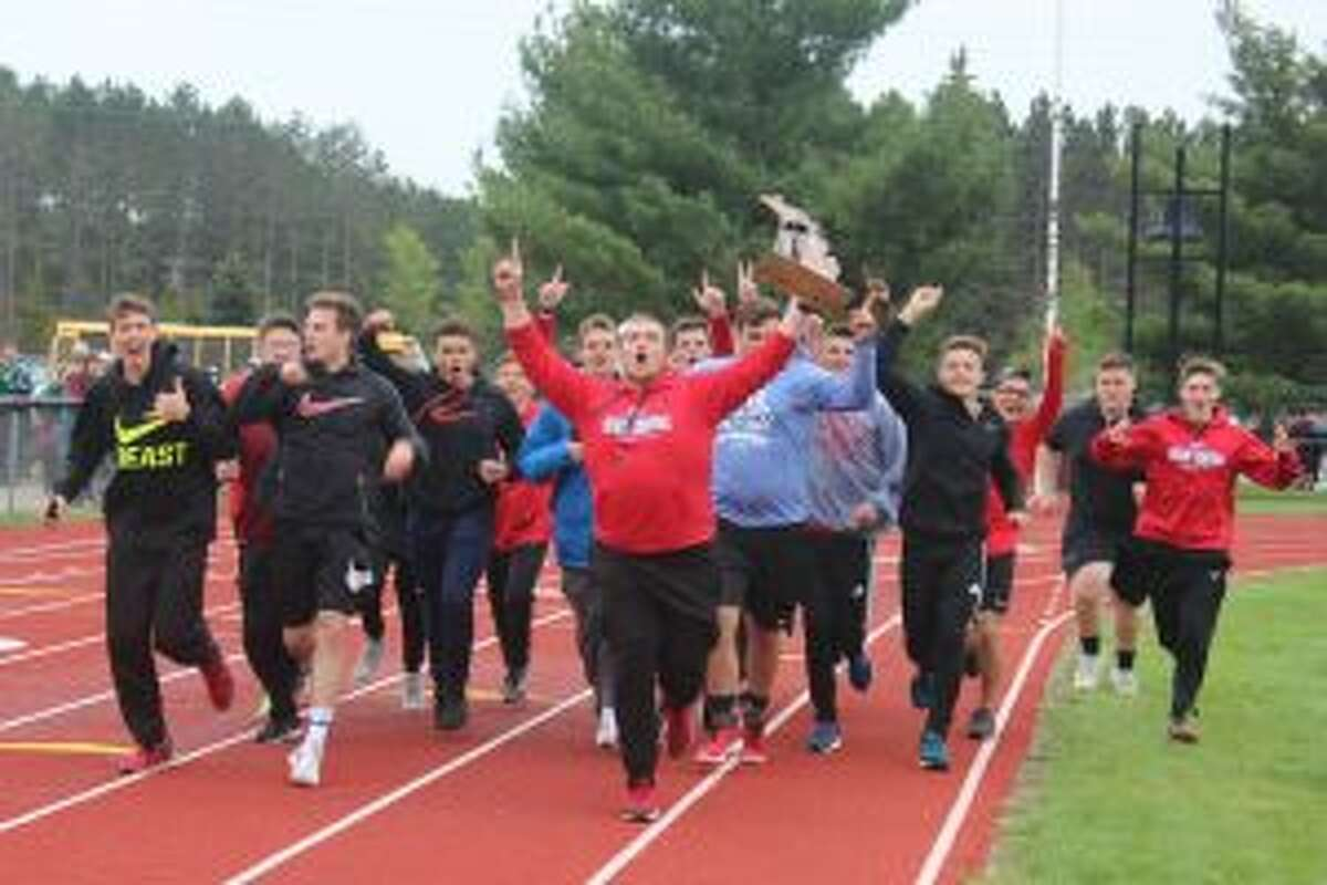 The Benzie Central boys track team enjoys a victory lap after winning the regional championship.
