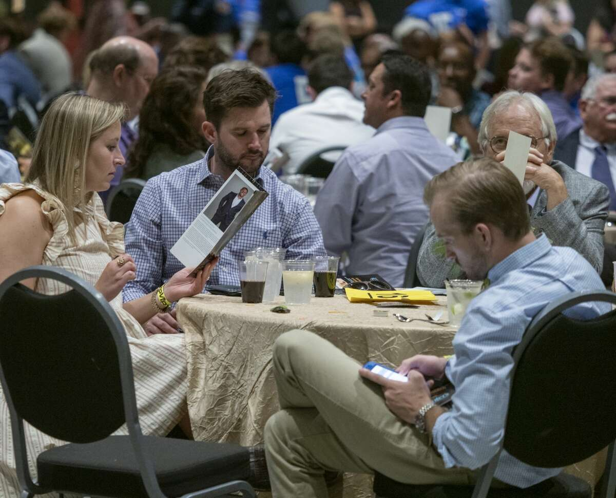 Guests read about and look over items available during the live auction 08/15/19 at the 19th annual Centers Stage presents an Evening with LaDainian Tomlinson. Tim Fischer/Reporter-Telegram
