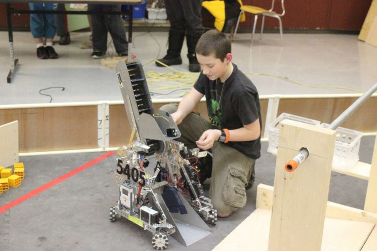 YOUNG ENGINEER: Benzie Central student Preston Mahan does some final work on the robot at the Robotic Team's open house. He was also named the team Rookie of the Year during the ceremony.