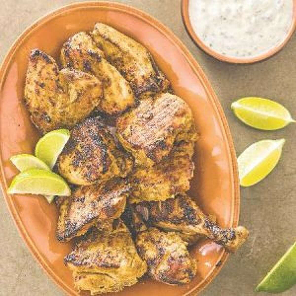 """This undated photo provided by America's Test Kitchen in May 2019 shows Tandoori Chicken with Raita in Brookline, Mass. This recipe appears in the cookbook """"Spiced."""" (Joe Keller/America's Test Kitchen via AP)"""