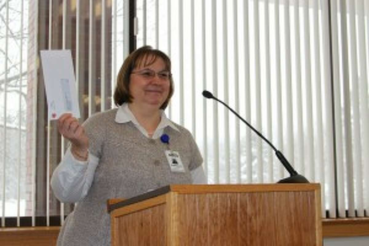 """REPAYMENT: Kathy Dube, administrator for The Maples Medical Care Facility, presents the final check to pay off loans the facility owes the county."""""""