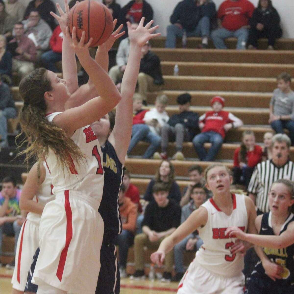 Bella Huddleston (10) powers to the basket during the second half of Benzie Central's loss to Cadillac, while Sierra Pallin (3) tries to box out for a potential rebound. (Photo/Robert Myers)