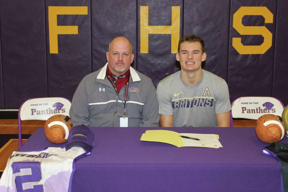 Conner Smith celebrates signing his letter of intent to play football for Albion with his high school coach Matt Stapleton. (Photo/Robert Myers)
