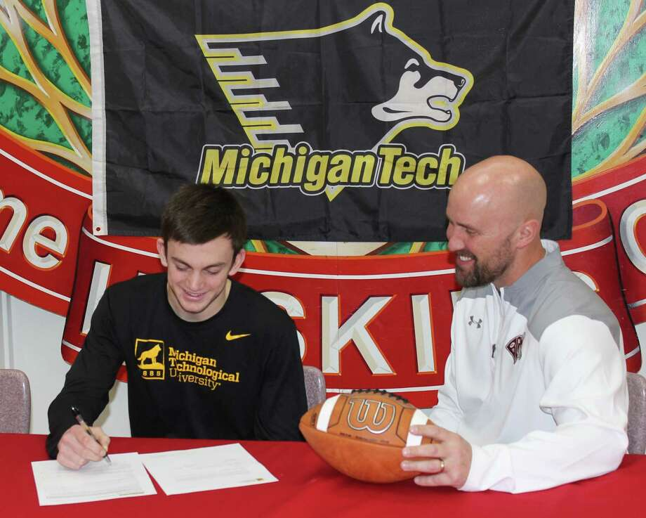 Benzie Central senior Tom Ross, joined by his high school coach Jason Katt, signs his letter of intent to play football for Michigan Tech, (Photo/Robert Myers)