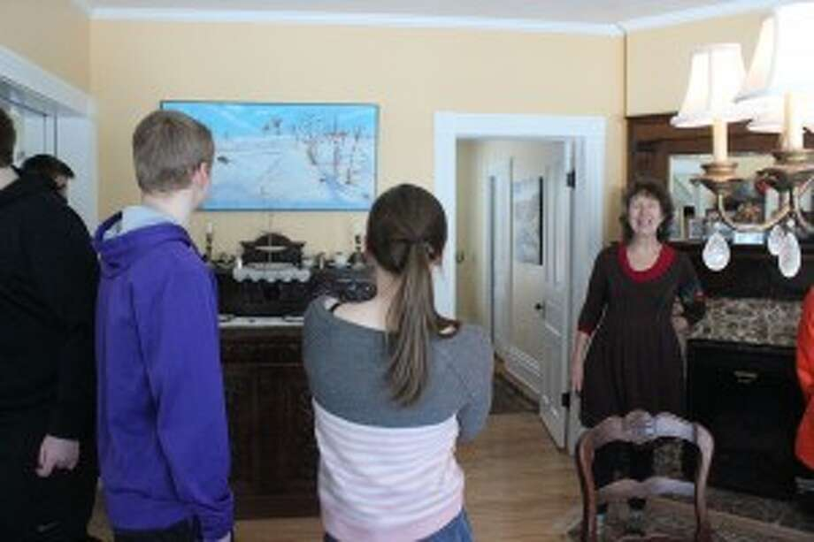 WINTER INSPIRATIONS: Local artist Ellie Harold shows her winter-inspired paintings to the visiting Frankfort students during their trip to her studio. (Photo/Bryan Warrick)