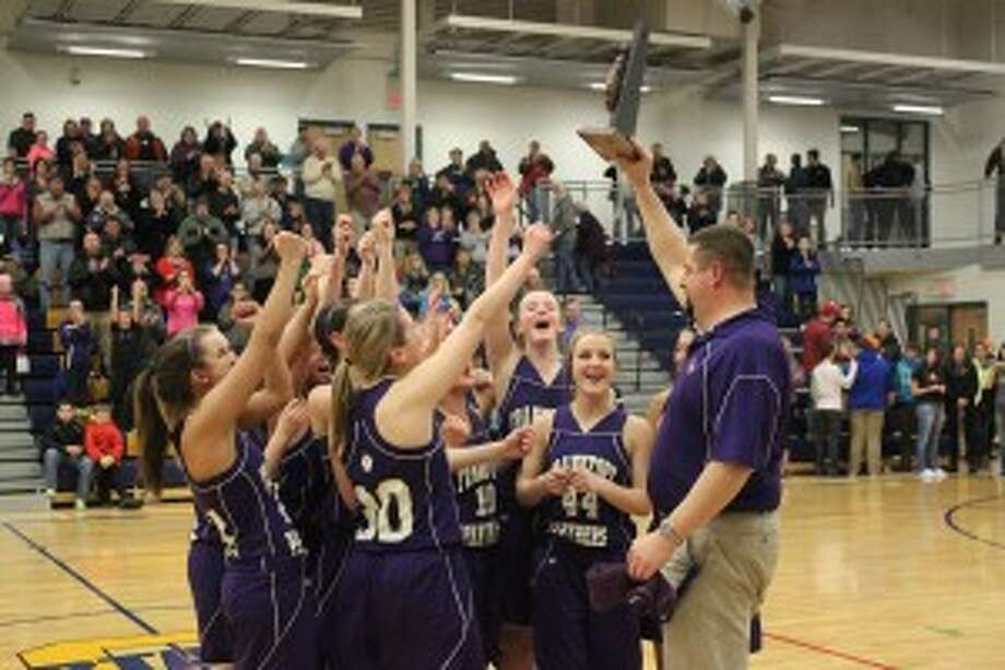 LEADING CHAMPIONS: Frankfort head coach Tim Reznich brings the district trophy to his team after winning the title. The Panthers went on to win the regional title too. Reznich was elected president of the Basketball Coaches Association of Michigan on March 6. (Photo/Bryan Warrick)