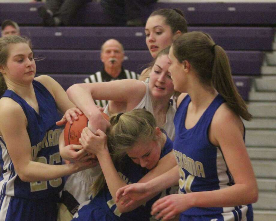 Emily Loney battles two Portagers for a rebound to force a jump ball call in late in the Panthers' loss to Onekama. (Photo/Robert Myers)