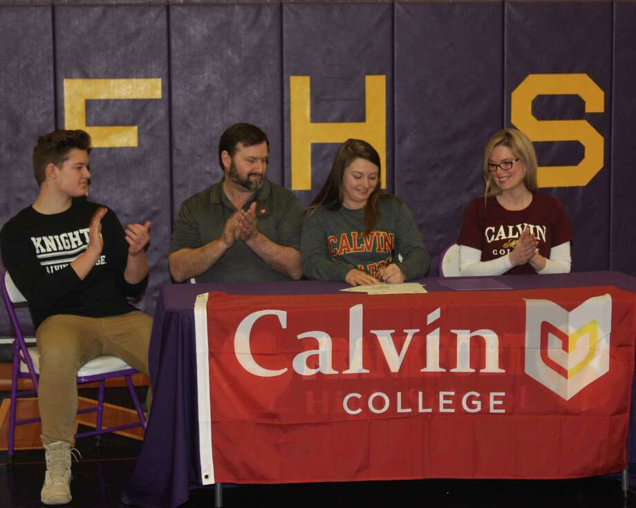Surrounded by her family, Frankfort senior Natalie Bigley signs her letter of intent to play college softball for Calvin College. (Photo/Robert Myers)