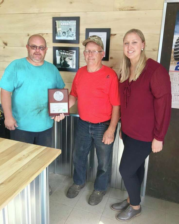 From left, current Bad Axe Tire Service owner Aaron Talaski, and founder Greg Talaski, pose with a plaque presented by Maddie Medkeff for 40 years of service. (Submitted Photo)