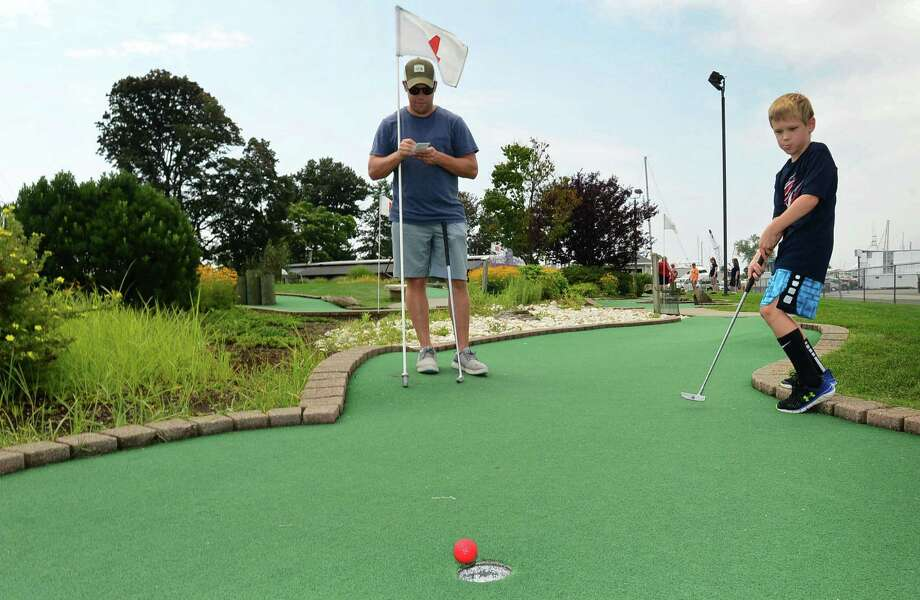 Westport resident Jeff Zuckerman plays Miniature Golf with his family including his son Will Zuckerman, 8, at Cove Marina Wednesday, August 14, 2019, in Norwalk, Conn. Photo: Erik Trautmann / Hearst Connecticut Media / Norwalk Hour