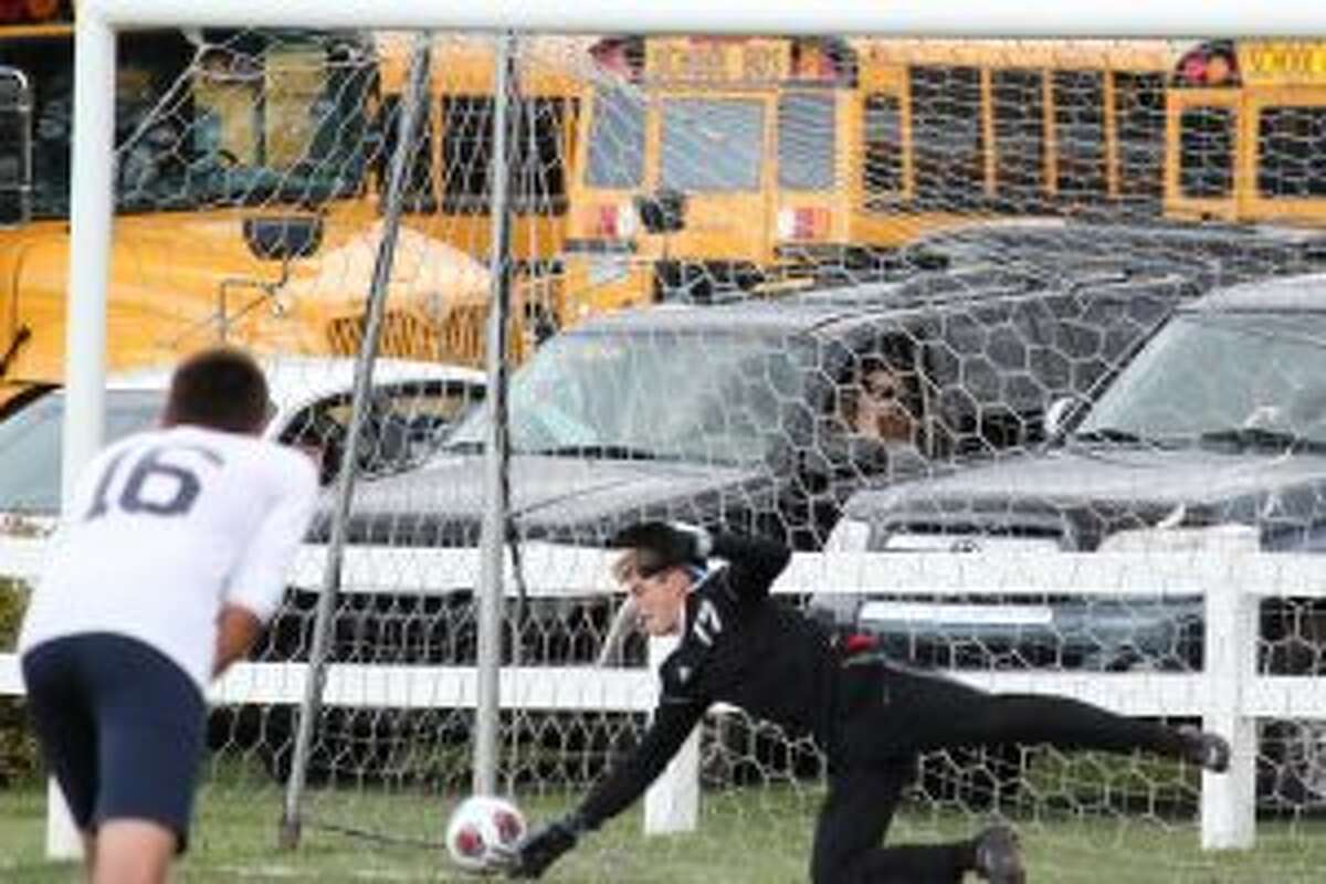 Jake Kennedy dives to his right to make a save on a penalty kick in the first half against Manistee. (Photo/Robert Myers)