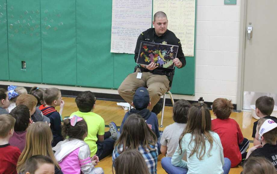 District school resource officer Dept. Geoff Miller reads to a group of students. (Photo/Robert Myers)
