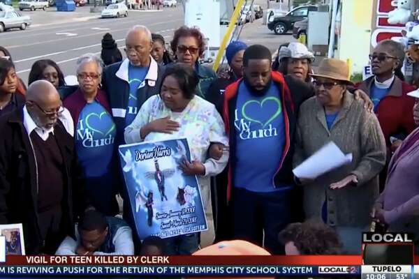 Dorian Harris's grandmother, Effie Fitch, center, honors Harris at a vigil at the Top Stop Shop last year