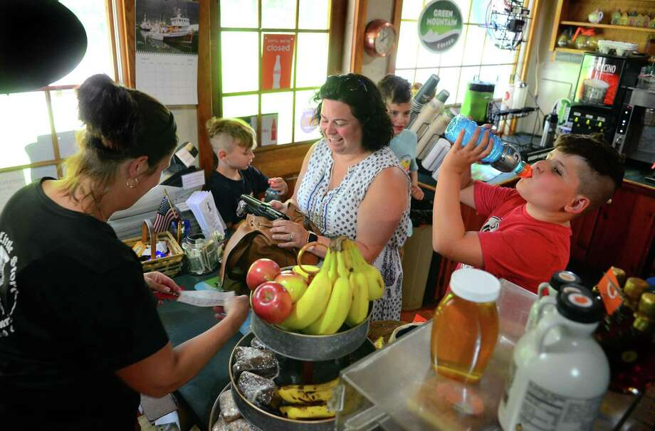Customer Kara Andrews, of Hamden, pays for drinks for her kids Grayson, 10, right, Lucas, 10, and Owen, 8, left, at The Little Store in Guilford on Thursday, Aug. 1. At far left is owner Melissa Munson. Photo: Christian Abraham / Hearst Connecticut Media / Connecticut Post