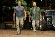 """This image released by Universal Pictures shows Dwayne Johnson, left, and Jason Statham in a scene from """"Fast & Furious Presents: Hobbs & Shaw."""" Movie going audiences have helped the """"Fast & Furious"""" spinoff """"Hobbs & Shaw"""" take another lap at No. 1 even with the onslaught of new movies this weekend. Universal Pictures estimated Aug. 11 that """"Hobbs & Shaw"""" added $25.4 million from North American theaters, bringing its domestic total to $108.5 million."""
