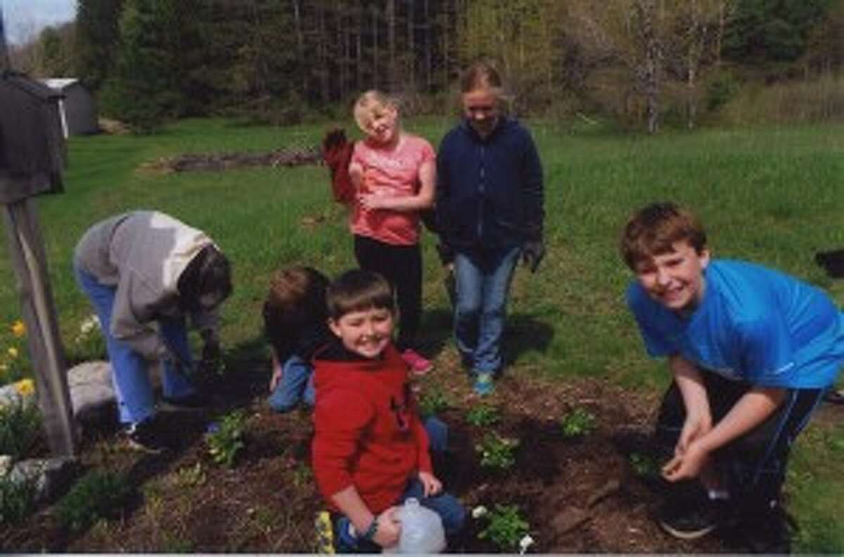 WORKING IN THE SUN: Fourth grade students from Platte River Elementary work with members of the Lake Shore Gardens Club around the school grounds. (Courtesy photo)