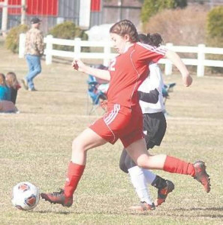 Isabel Pataky (12) battles to clear the ball from the defensive end. (Photo/Robert Myers)
