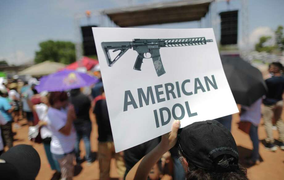 A demonstrator holds a sign depicting an assault rifle at a protest against President Trump's visit, following a mass shooting which left at least 22 people dead, on August 7, 2019 in El Paso, Texas. Protestors also called for gun control and denounced white supremacy. Trump is scheduled to visit the city today. A 21-year-old white male suspect remains in custody in El Paso which sits along the U.S.-Mexico border. (Photo by Mario Tama/Getty Images) Photo: Mario Tama, Staff / Getty Images / 2019 Getty Images