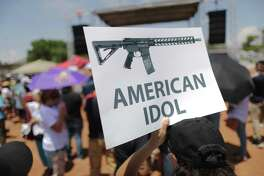 EL PASO, TEXAS - AUGUST 07: A demonstrator holds a sign depicting an assault rifle at a protest against President Trump's visit, following a mass shooting which left at least 22 people dead, on August 7, 2019 in El Paso, Texas. Protestors also called for gun control and denounced white supremacy. Trump is scheduled to visit the city today. A 21-year-old white male suspect remains in custody in El Paso which sits along the U.S.-Mexico border. (Photo by Mario Tama/Getty Images)