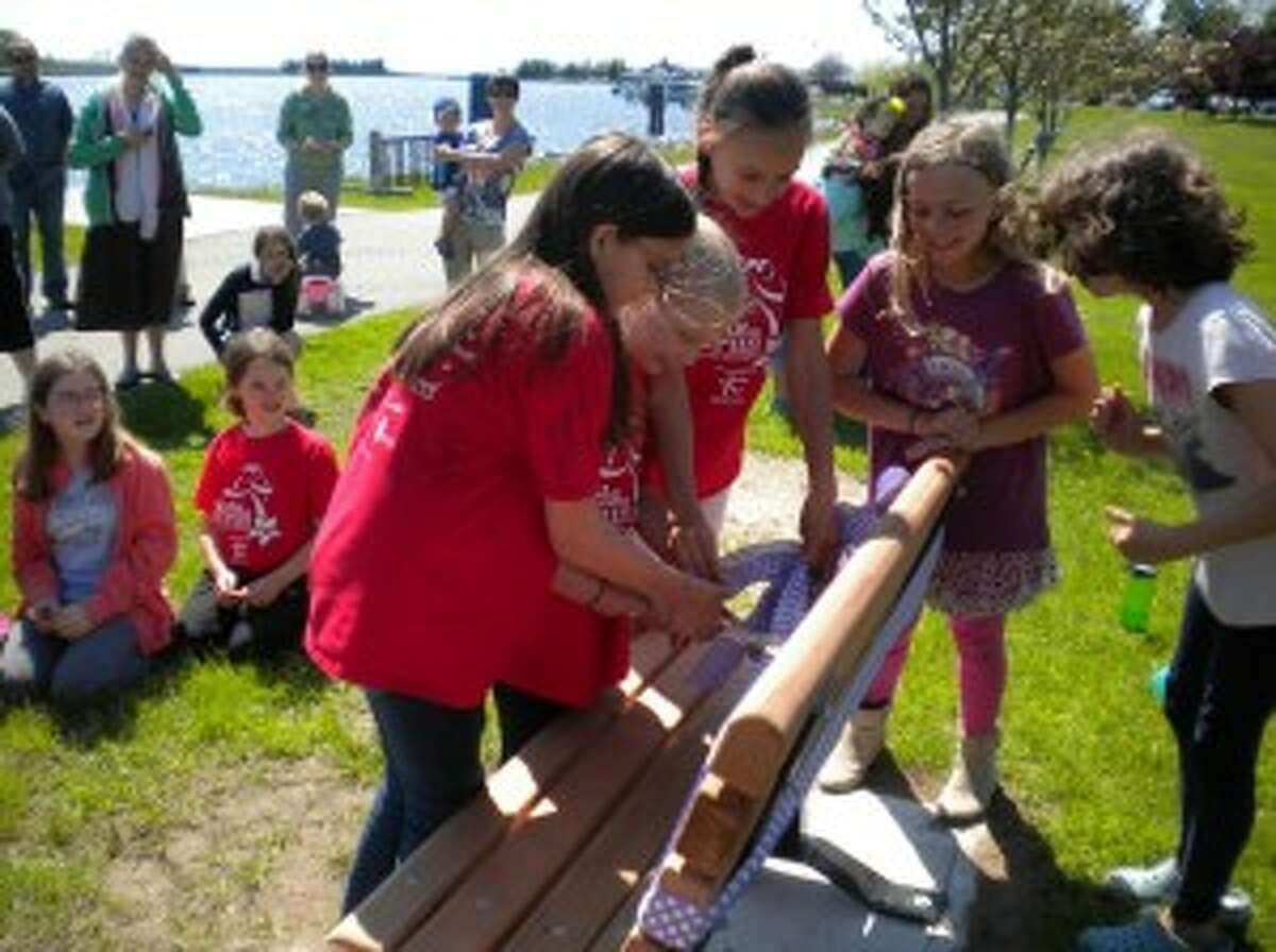 GIFT TO CITY: Members of the Girls on the Run team cut the ribbon on the new bench they bought for the Betsie Valley Trail in downtown Frankfort.