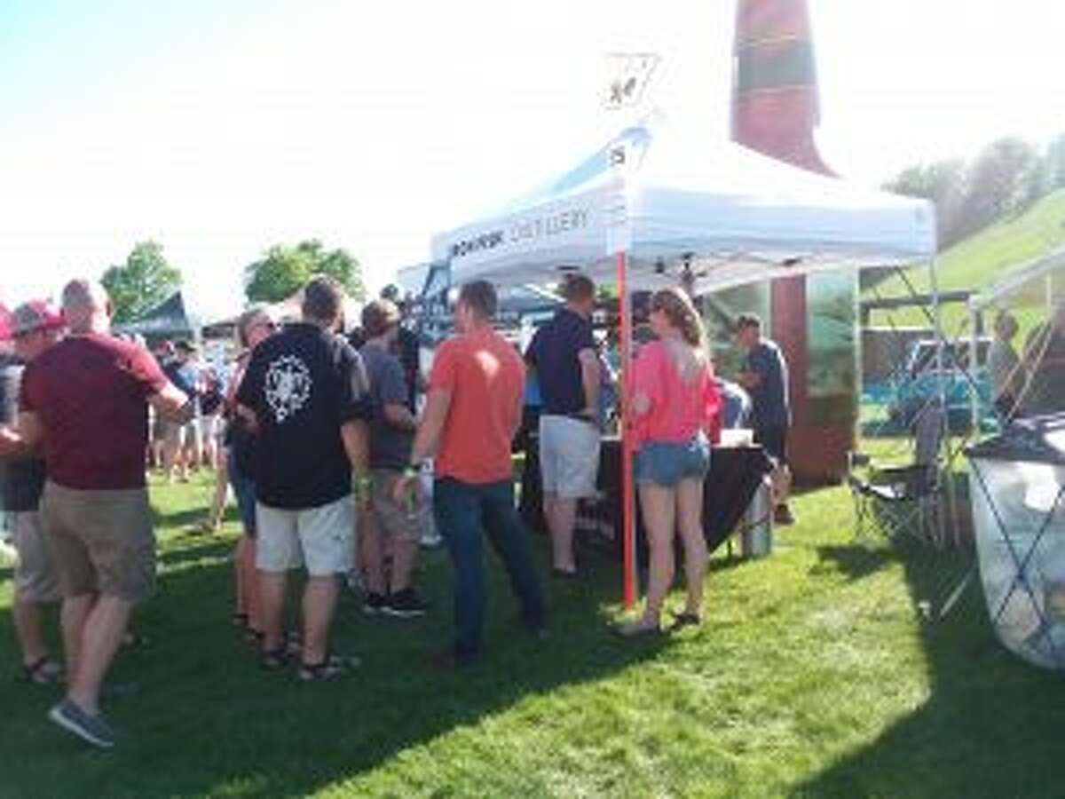 Crowds line up to get a drink from the Iron Fish Distillery tent.