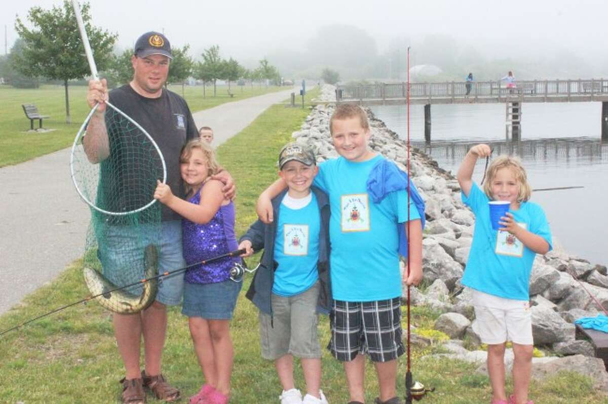 ENJOYING THEOUTDOORS: Kids show off their catches, including a nightcrawler caught the day before. Take a Kid Fishing Day is meant to get kids outside and having fun. This year's event is set for Friday and Saturday.