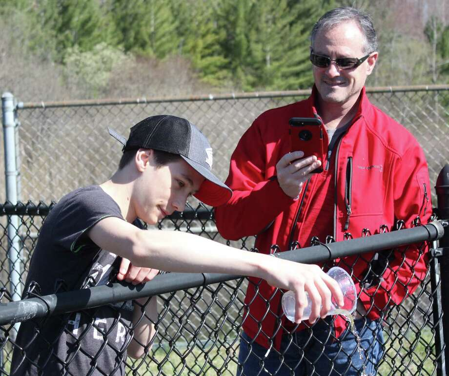 Benzie Central principal Dave Clasen live streams the salmon release on the school Facebook page. (Photo/Robert Myers)