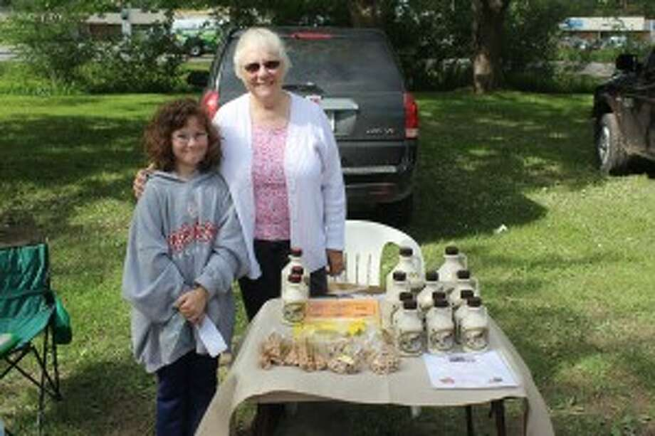 SERVING UP SWEETS: Jessica Whaley, left, and Ginny Markus work a table at the Honor Farmers Market, selling syrup and nut. Whaley also makes bookmarks for visitors. (Photos/Bryan Warrick)