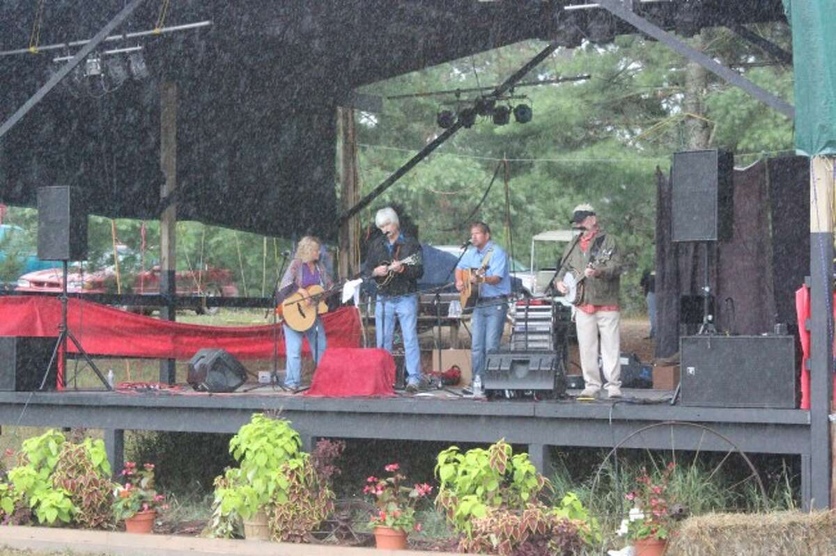 PLAYING THROUGH THE RAIN: Last year's Dunesville Festival had to deal with a lot of rain, but the bad weather didn't stop the bands from playing and the visitors from having fun. (photo/Bryan Warrick)