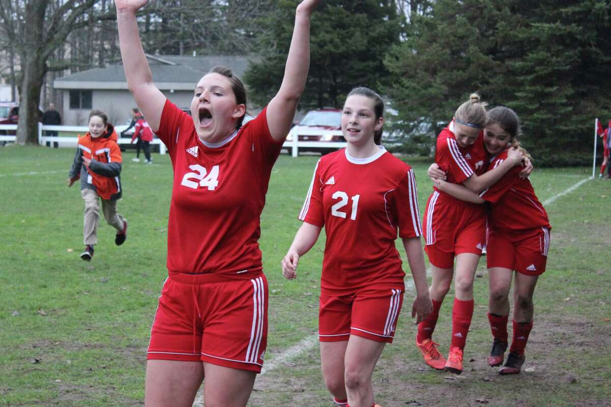 Benzie Central girls soccer players celebrate their first win of the spring. (Photo/Robert Myers)