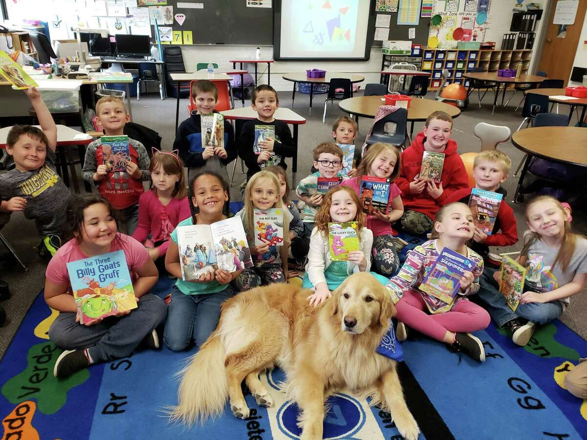 Kim Gramzow's first grade students at Betsie Valley Elementary visit enjoy a visit from Fisher during the Benzie Sunrise Rotary's third reading visit of the school year. (Courtesy photo)