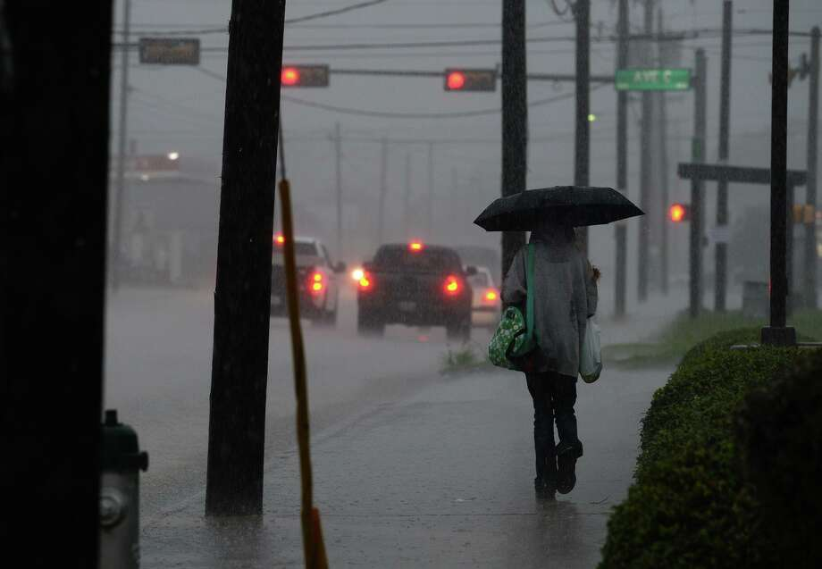 A woman walks along on College Street during Friday morning's down pour.  Photo taken Friday, 8/16/19 Photo: Guiseppe Barranco/The Enterprise, Photo Editor / Guiseppe Barranco ©