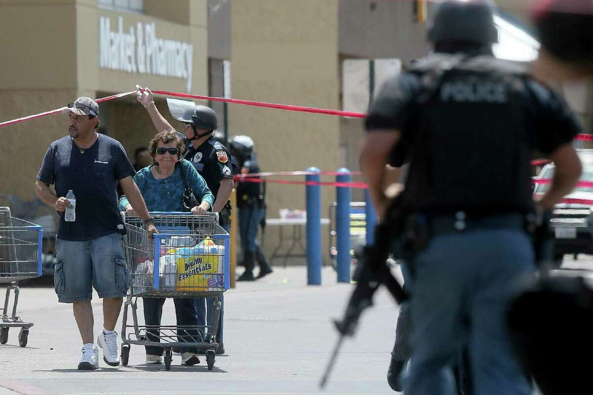 Walmart customers are escorted from the store after a gunman opened fire on shoppers near the Cielo Vista Mall, Saturday, Aug. 3, 2019, in El Paso, Texas. Multiple people were killed and one person was in custody after a shooter went on a rampage at a shopping mall, police in the Texas border town of El Paso said. (Mark Lambie/The El Paso Times via AP)