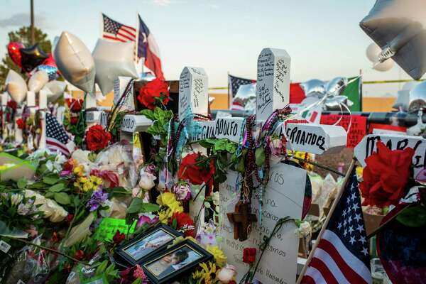 "Flowers lay near wooden crosses during a vigil outside a Walmart Inc. retail store following a mass shooting in El Paso, Texas, U.S., on Tuesday, Aug. 6, 2019. President Donald Trump endorsed an expansion of background checks for U.S. gun buyers following the massacres in El Paso, Texas, and Dayton, Ohio, but said there's ""no political appetite"" to renew a ban on military-style rifles. Photographer: Luke E. Montavon/Bloomberg"