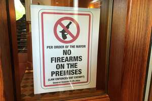 The city has posted signs noting that firearms are banned at City Hall and the municipal Hall of Records.