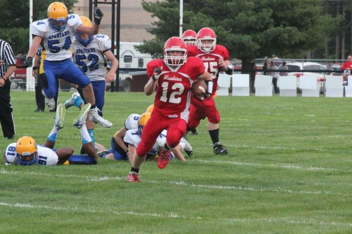 DODGING DEFENSE: Benzie Central player Zach Drake (12) runs past the Mason County Central defense during the season opener. (Photos/Bryan Warrick)