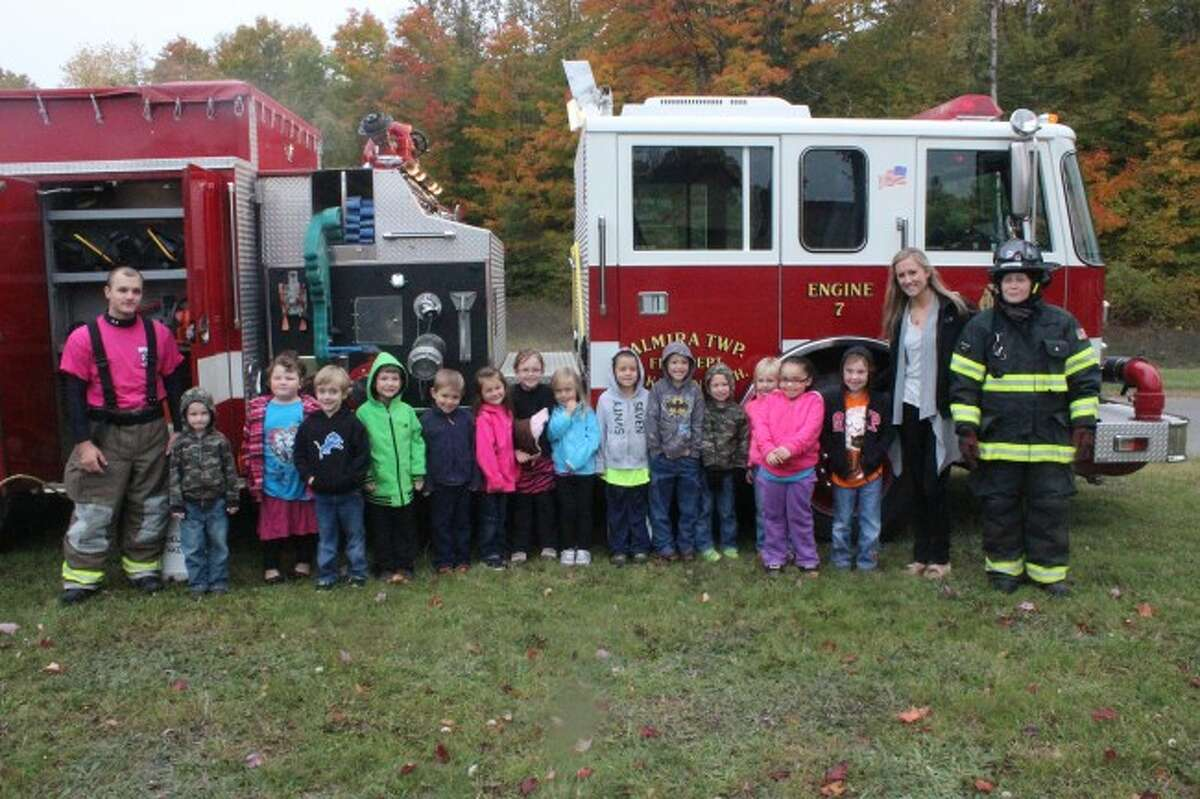 BIG VISITOR: Students in Carrie Urbain's kindergarten class stand in front of the visiting firetruck with the firefighters during the Fire Prevention event at Lake Ann Elementary. (Photos/Bryan Warrick)