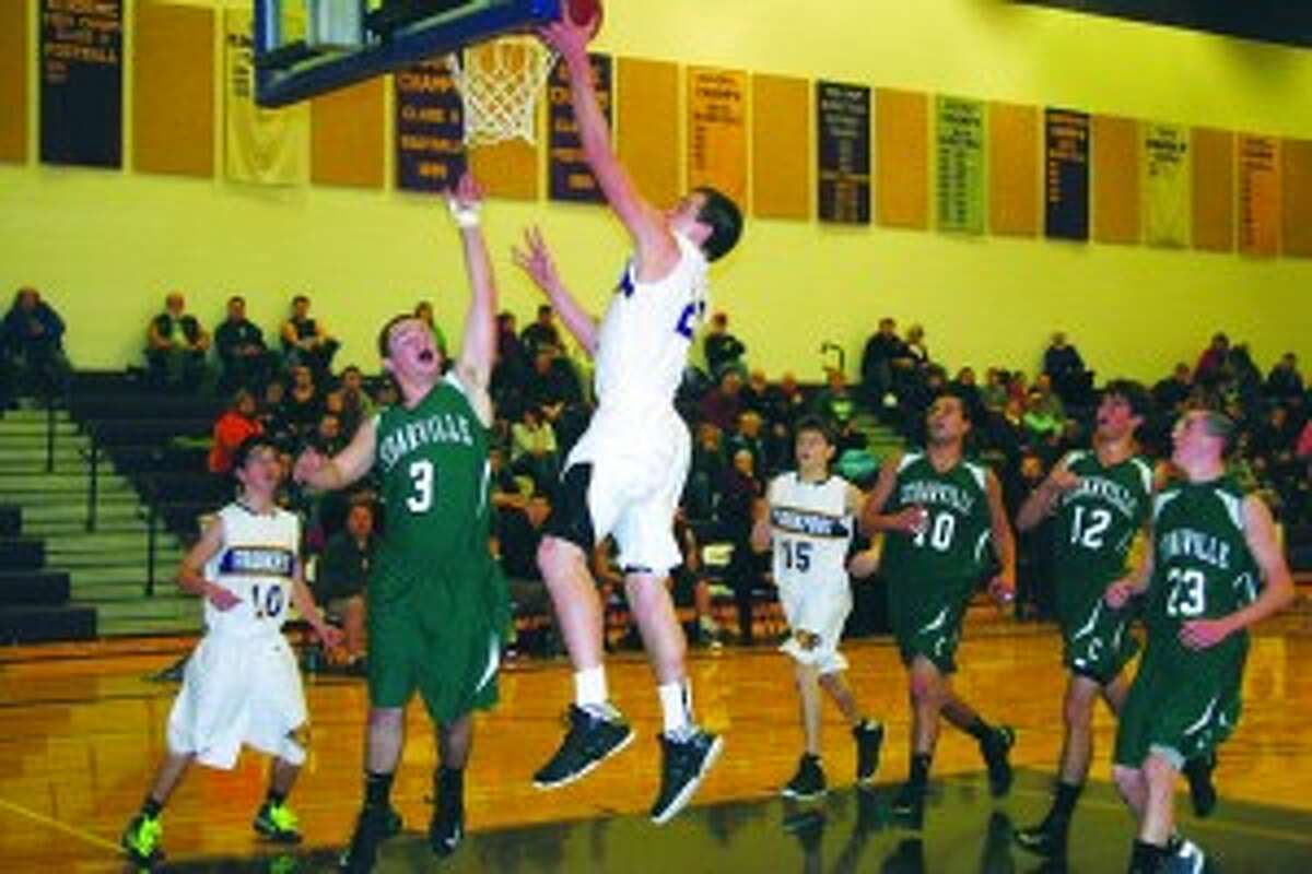"""OVERCOMING CHALLENGES: Sophomore David Loney puts the ball in with a big jump. He led the team in scoring with 20 points."""""""
