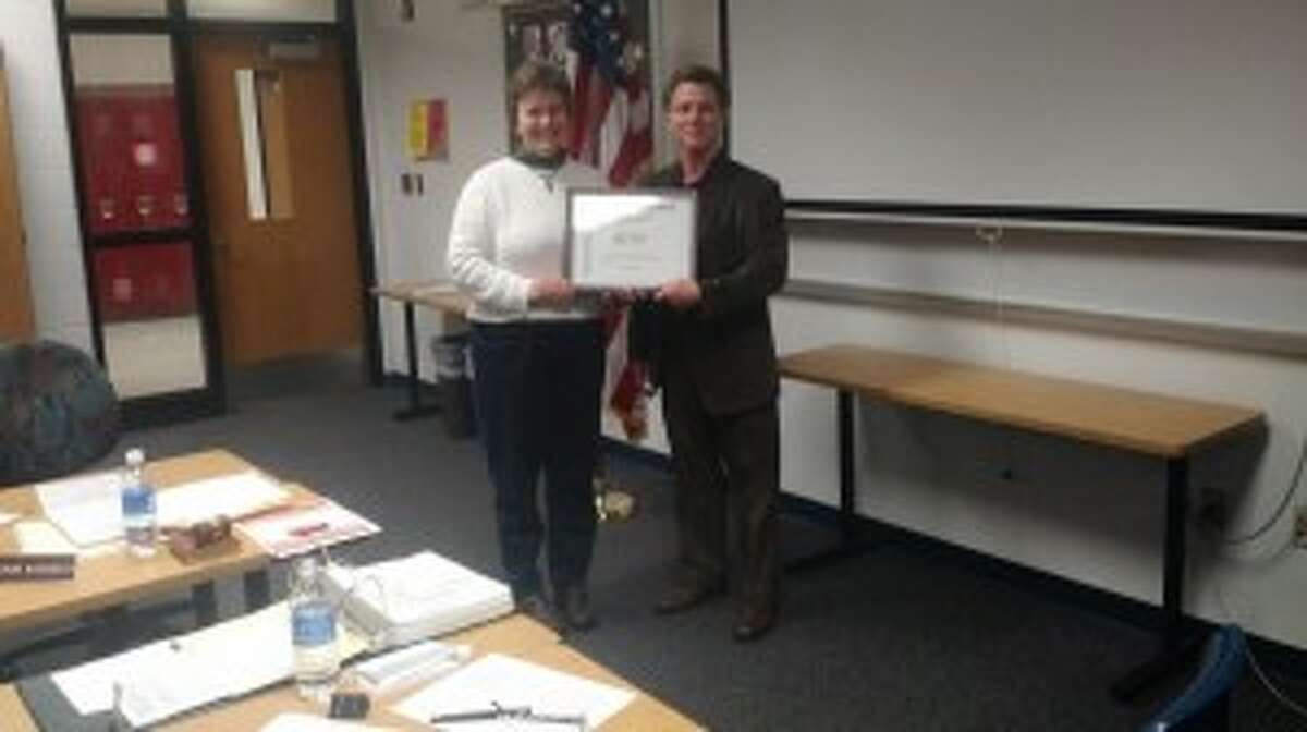 SCHOOL HONORS: Benzie Central Board of Education President Lorraine Nordbeck presents the Advanced Placement Honor Roll certificate to high school principal Larry Haughn at the Dec. 8 board meeting. The school earned recognition for its students' success in AP classes. (Photo/Bryan Warrick)