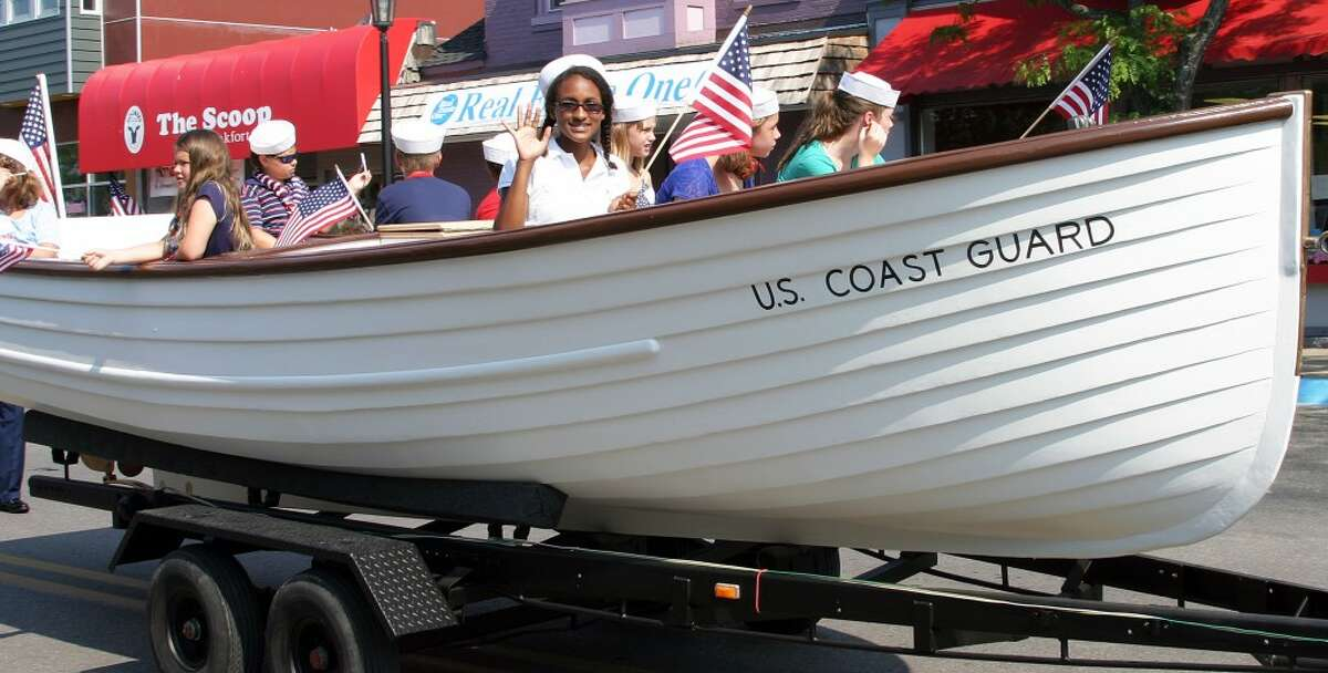 'ROLLING EXHIBIT': Jon Hawley, president of Friends of Point Betsie Lighthouse, hauled the Coast Guard lighthouse tender boat in the 4th of July Parade. The boat is on display at the lighthouse. (Photo/Roland Halliday)