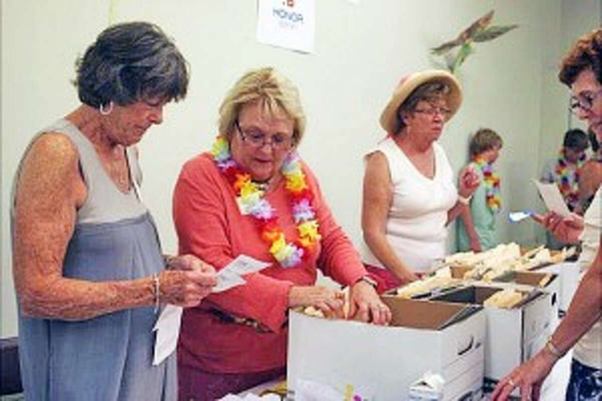 GARDEN PARTY: Kathy Schultz, Diane Wilbur and Judy Grant process winning bidders from both the live and silent auctions at The Garden Party.